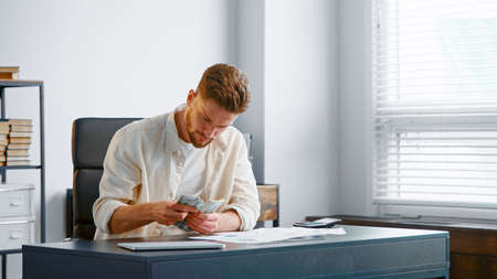 Concentrated company manager with beard counts money banknotes and looks at sheets of papers checking with reports on table Фото со стока