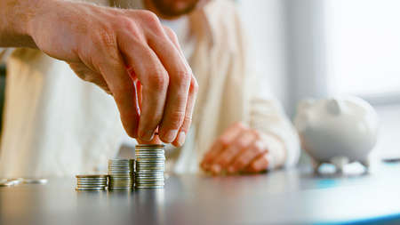 Careful guy company manager puts saved silver coins on stack on gray office table against blurred piggy bank at home closeup
