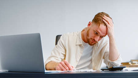 Concentrated and worried manager looks at paper checks and total sum on calculator and puts head in hand at table with laptop