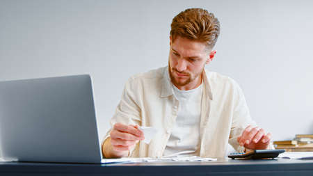 Skilled accountant looks at paper checks and summarizes total on calculator sitting at table with white laptop in bank office Imagens