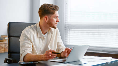 Young man with beard pays online holding credit card and typing on white laptop on gray table in bank office
