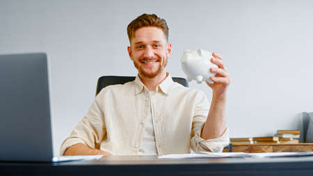 Bearded guy company manager in yellow shirt holds white piggy bank and smiles posing at table with papers and laptop in office