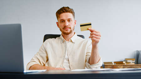 Serious man corporate company manager with beard holds yellow bank card and smiles joyfully posing at office table with laptop