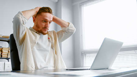 Depressed guy in yellow shirt looks at laptop with lost internet connection holding hands on head sitting at table with papers