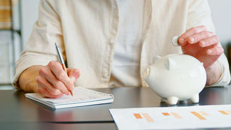 Unrecognizable person in yellow shirt writes in paper notebook and strokes gently large white piggy bank sitting at office table