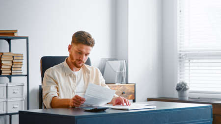 Concentrated businessman with beard reads report from sheets of paper with thoughtful face sitting at gray table in office Фото со стока