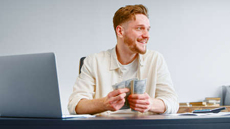 Smiling businessman counts cash income holding dollar banknotes sitting at table with white laptop and calculator Фото со стока