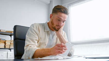 Shocked man bank accountant with beard looks at paper checks and puts hand on head after sorting receipts on table in office