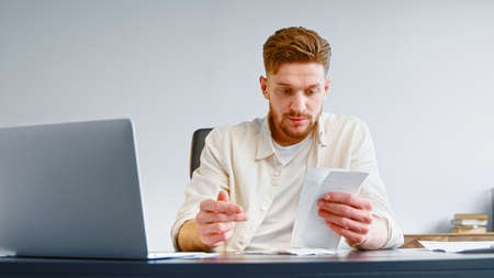Bearded professional accountant sorts paper invoice receipts sitting at table with white laptop in company office closeup Фото со стока