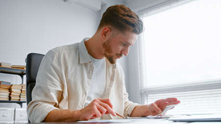 Bearded guy experienced accountant summarizes income comparing invoice receipts with reports on calculator with joyful smile