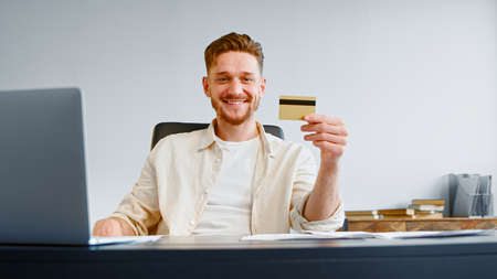 Smiling guy successful company manager with beard holds credit card and poses sitting at gray table with laptop and papers