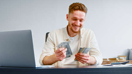 Smiling self employed businessman counts cash income holding dollar banknotes sitting at table with white laptop and calculator