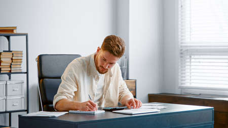 Bearded accountant sums up unexpected expenses from checks on calculator and writes results in paper notebook sitting in office