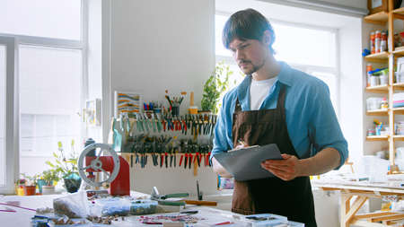 A young master conducting inventory in a creative studio. A man in an apron with clipboard at work