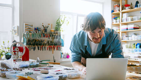 Young master typing a message on a laptop in the studio. Man in an apron surfing the internet using a laptop