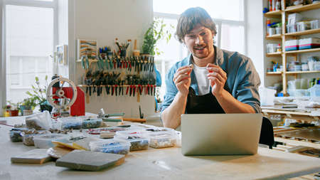 Happy man conducts training online using a laptop in the studio. Young male in an apron talking by video call in a workshop