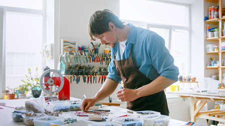 Young master in an apron at work in his workshop. Working man with mosaic in studio