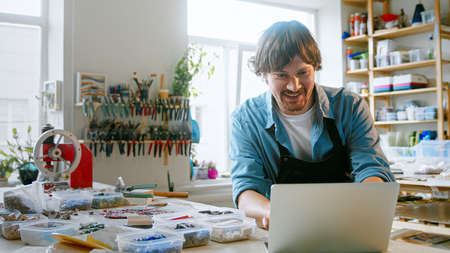 Smiling man typing on laptop in mosaic workshop Фото со стока