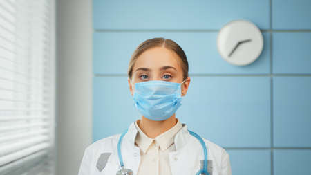 Young woman general practitioner in white coat and blue disposable face mask looks straight standing in hospital office room close view Фото со стока