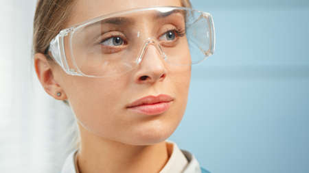 Exhausted young woman medical nurse in protective glasses looks straight standing in hospital room under bright sunlight close view