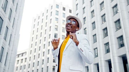 African American performer in white suit and yellow t shirt dances on square among highrise megalopolis buildings low angle shot