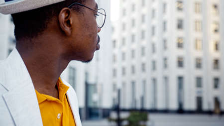 African American guy in glasses takes photo of local highrise office building on smartphone standing on city street close view