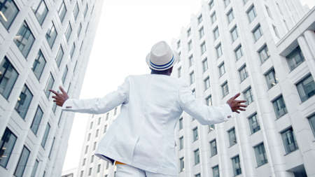 Afro American guy in white suit and Fedora hat walks along gray pavement dancing and listening to music in headphones backside view