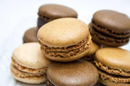 Vanilla, coffee and chocolate flavor french macaroons on a white plate photo