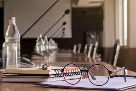 Glasses, pen, pencil, and notebooks in meeting room
