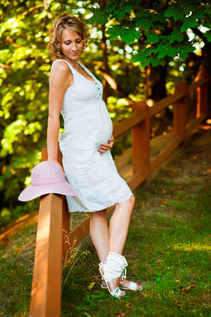Pregnant woman standing near fence with hat Stock Photo - 11692850