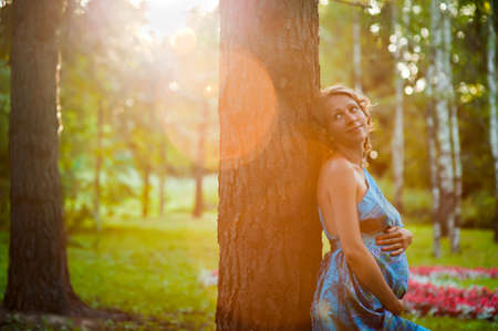 demographics: Beautiful young pregnant woman near tree in park Stock Photo