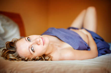 Young pregnant woman lies on the bed photo