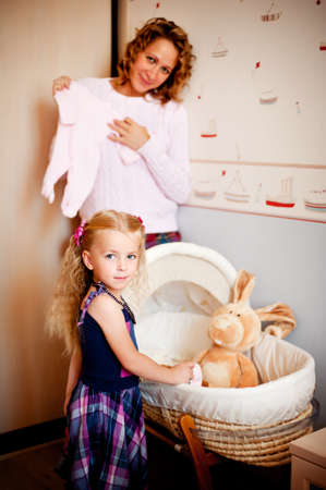 however: Pregnant woman and her daughter standing near the baby cradle