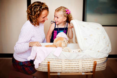 however: Happy pregnant mother and her daughter sitting near baby cradle Stock Photo