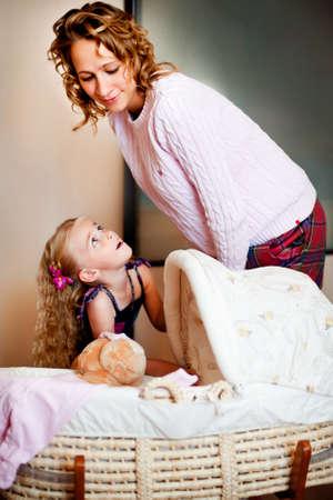 demografia: Joven madre y su hija riéndose cerca de cuna