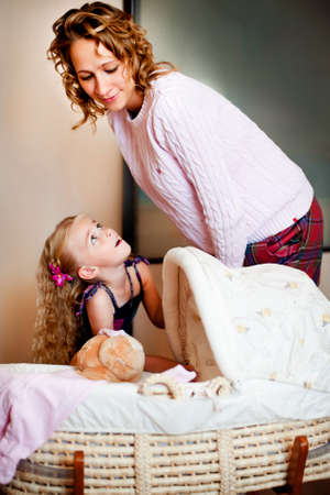 however: Young mother and her laughing daughter near baby cradle