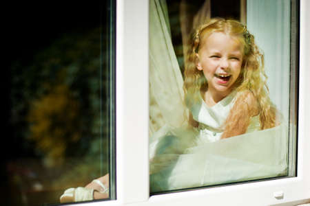 looking through window: Funny laughing girl looking through window
