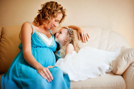 Pregnant woman and her charming daughter on sofa close to each other photo
