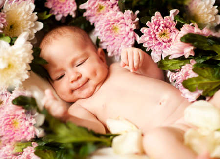Charming smiling baby in flowers Stock Photo