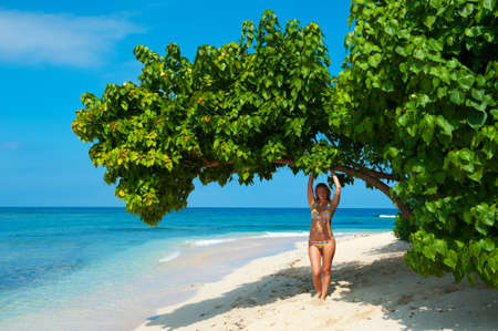 Beautiful young woman in colorfull swimsuit on exotic beach photo