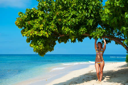 haiti: Charming young woman in colorfull swimsuit on exotic beach