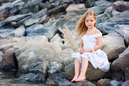 little girl sitting: Lonely beautiful girl sitting on stone sea shore and thinking