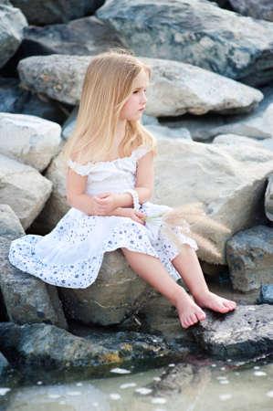 Sad Lonely beautiful girl sitting on stone sea shore and thinking photo