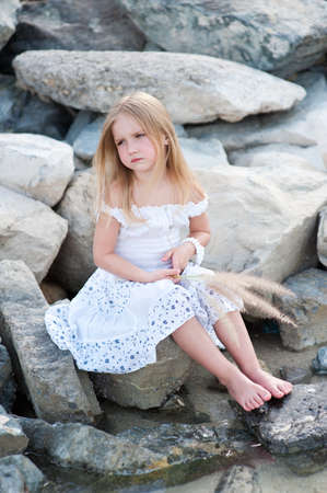 lonely girl: Lonely beautiful girl sitting on stone sea shore with grass in hands