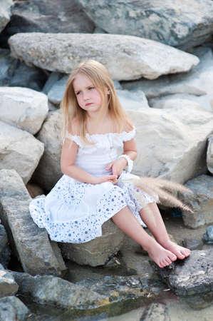 petite fille triste: Solitaire belle fille assis sur le rivage de la mer de pierre avec de l'herbe dans les mains