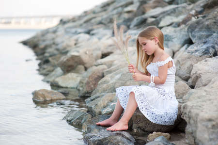 Lonely beautiful girl sitting on stone sea shore with grass in hands photo