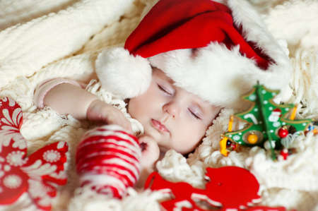 Angelic infant in santa hat sleeping and having christmass and new year photo