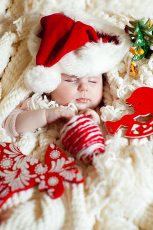 Angelic infant in santa hat sleeping and having christmass photo