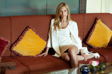 Beautiful blond woman sitting on sofa in white suit  photo