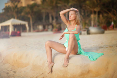 hot girl legs: Young blond female sitting on tropical beach with sand in dress watching horizont Stock Photo